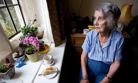 Elderly woman looks out of the window