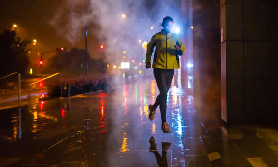 Female jogger running on rainy night in the city.