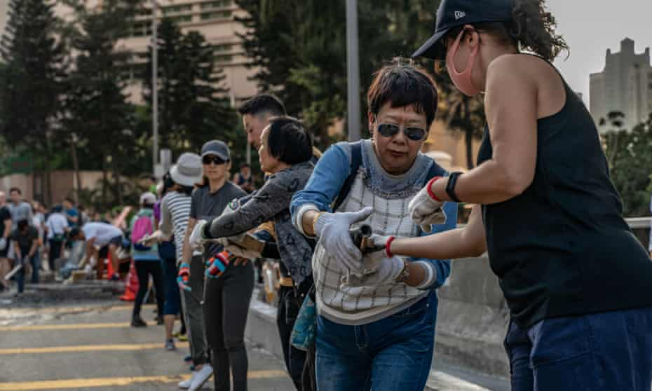 Residents form a human chain to clear debris from a concrete barricade.