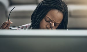 A young woman suffering stress at a computer