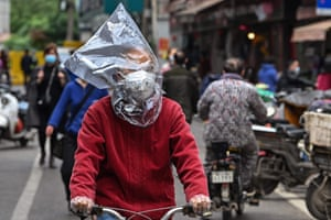 A man wearing a face mask and a plastic bag on his head in Wuhan, China