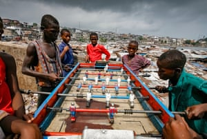 """Freetown, Sierra Leone. Longitude: -13° 22' 75.45"""" Boys play table football on the edge of the Mabella slum in Susan's Bay, home to about 19,000 people"""