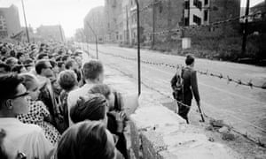West Berliners watch an East German soldier on patrol on the other side of the Berlin Wall in 1961.