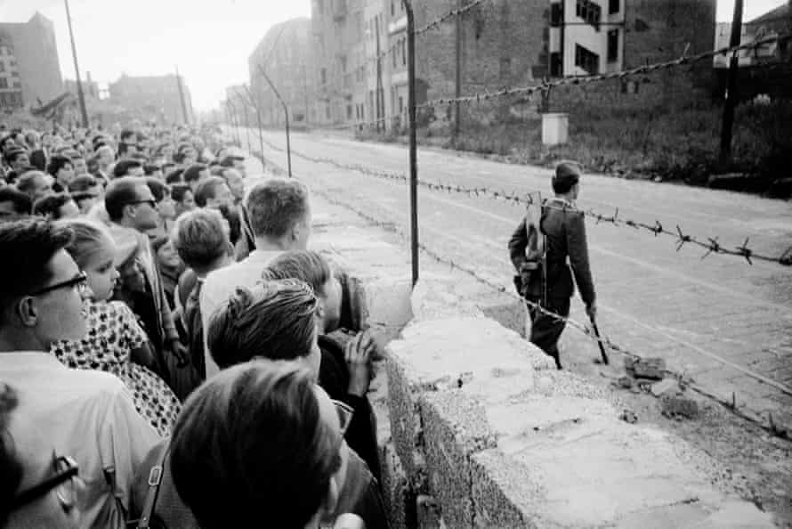 A crowd of West Berliners gather at the Berlin Wall while an East German soldier patrols on the other side, Berlin, Germany, August 1961.
