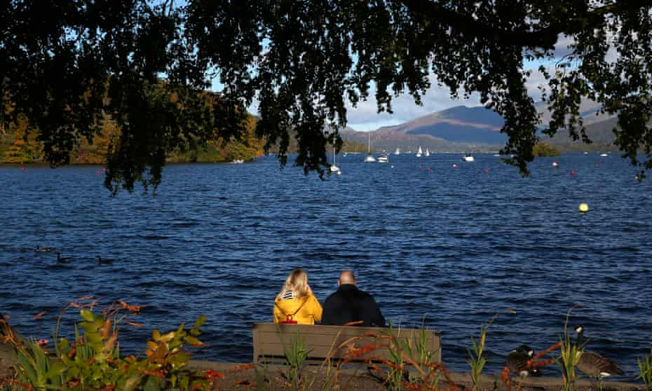 A couple look out towards Lake Windermere from Bowness-on-Windermere on October 10, 2020 in Windermere, England