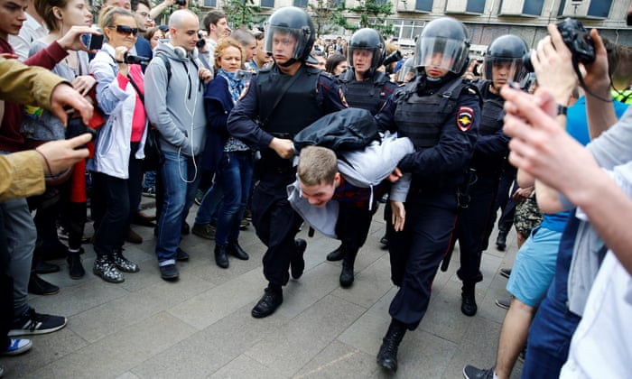 Russian police officers take into custody a protester during an unauthorised opposition rally in Moscow in June last year