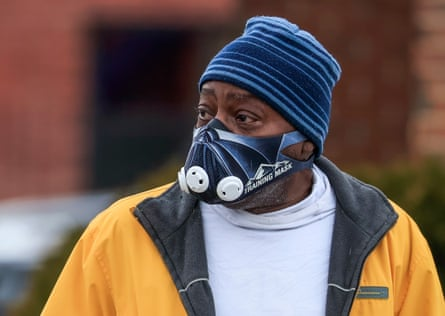 A man wears a protective face mask as he walks through the predominately black south side of Chicago.