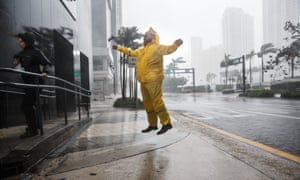 Weather reporters jump to illustrate the force of the winds caused by Hurricane Irma as it arrives in Miami.