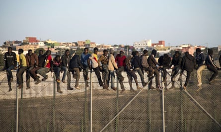 Migrants on a border fence separating Morocco from the Spanish enclave of Melilla