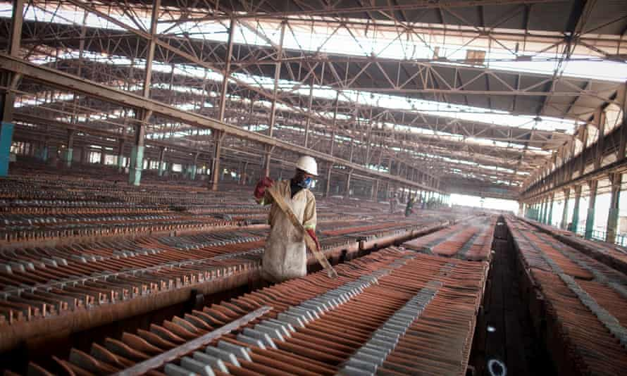 A worker handles copper sheets during electrolytic refining at the metallurgical plant in Katanga