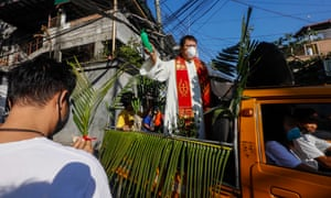 A Catholic priest wearing a protective mask travels in a vehicle to bless devotees and fronds during Palm Sunday in Quezon City, Metro Manila, Philippines, 05 April 2020.