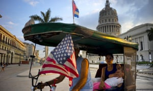 A taxi pedals his bicycle, decorated with Cuban and US flags near El Capitolio in Havana, Cuba, on Tuesday. Barack Obama will travel there on Sunday.