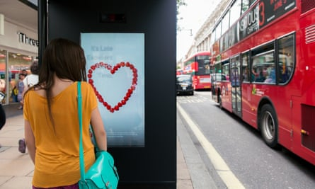 A passerby looks at the M&C Saatchi Artificial Intelligence poster in Oxford Street London.