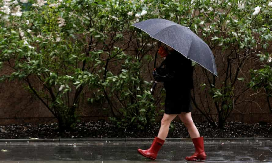 A woman walks through the wind and rain during the morning commute in New York City.