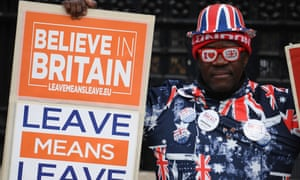 A pro-Brexit demonstrator hold placards as he stands outside the Houses of Parliament in central London