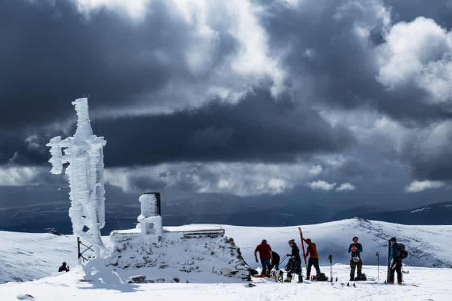 """Mayday. """"Ne'er cast a cloot till May be oot!"""" Fresh showers of snow re-coated Cairngorm summit as cross country and touring skiers pause at the summit weather station to eat lunch and prepare for the descent."""