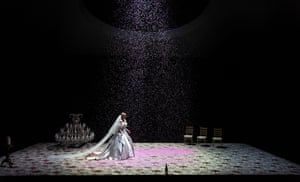 A woman in a wedding dress walks across a stage covered in confetti