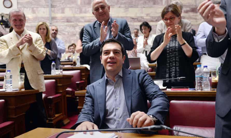 Greek prime minister Alexis Tsipras is applauded by lawmakers before addressing his parliamentary group meeting in Athens.