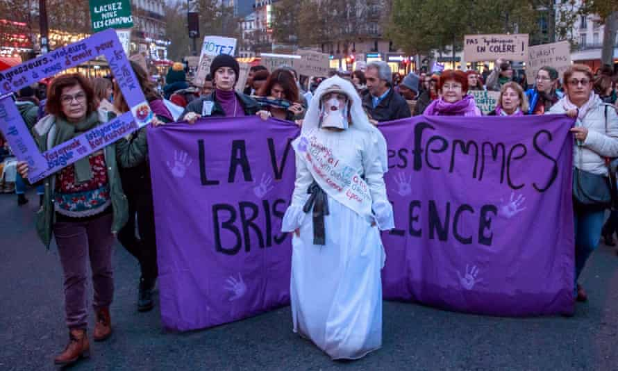 Women in Paris carrying signs saying 'All of us [women]' protest against sexual violence.
