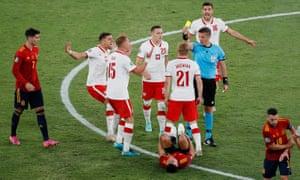 Poland's Kamil Jozwiak is shown a yellow card by referee Daniele Orsato.