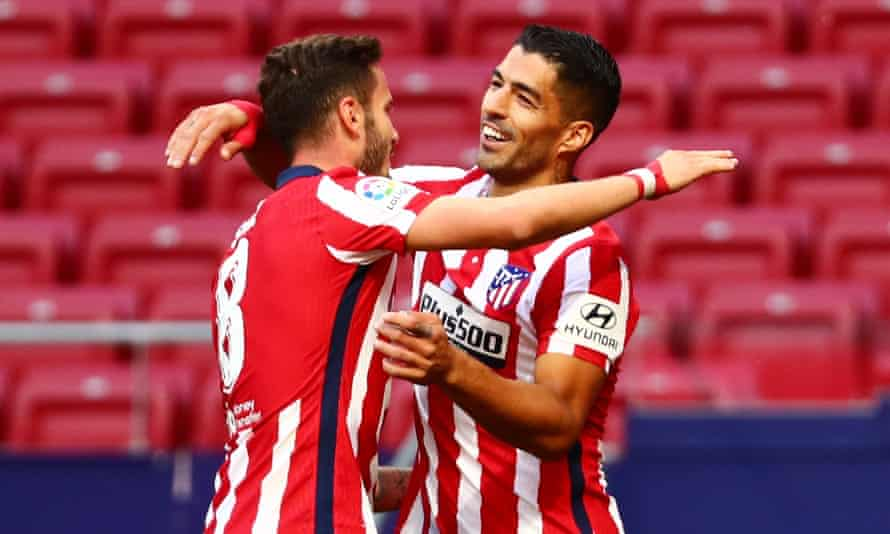 Luis Suárez (right) celebrates with Saúl Ñíguez after scoring the second of his two goals on his debut for Atlético Madrid.