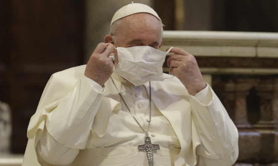 Pope Francis puts on a face mask as he attends a ceremony in the Basilica of Santa Maria in Aracoeli, in Rome
