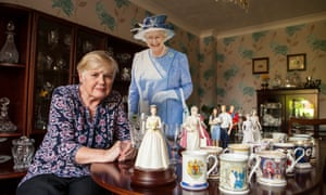Liz sitting at a table with mugs and figurines, and a big cardboard cut-out of the queen behind her