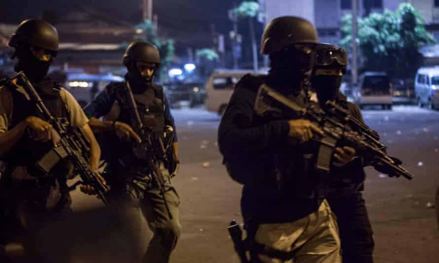 Indonesian police officers stand guard at the site of twin bomb explosions at Kampung Melayu bus station on Wednesday.