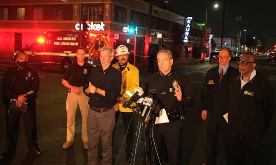 Michel Moore, center, talks to the media after illegal fireworks seized at a South Los Angeles home exploded.