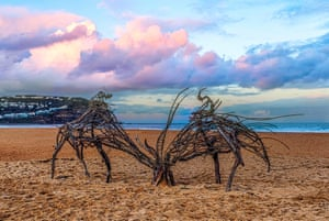 Two driftwood sculptures on the sand