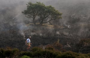 A firefighter tackling the wildfire on Saddleworth Moor amongst the scorched earth