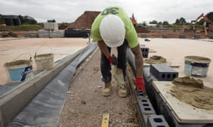 A worker positions brickwork at a Willmott Dixon housing development construction site at Ashton Rise, near Bristol.