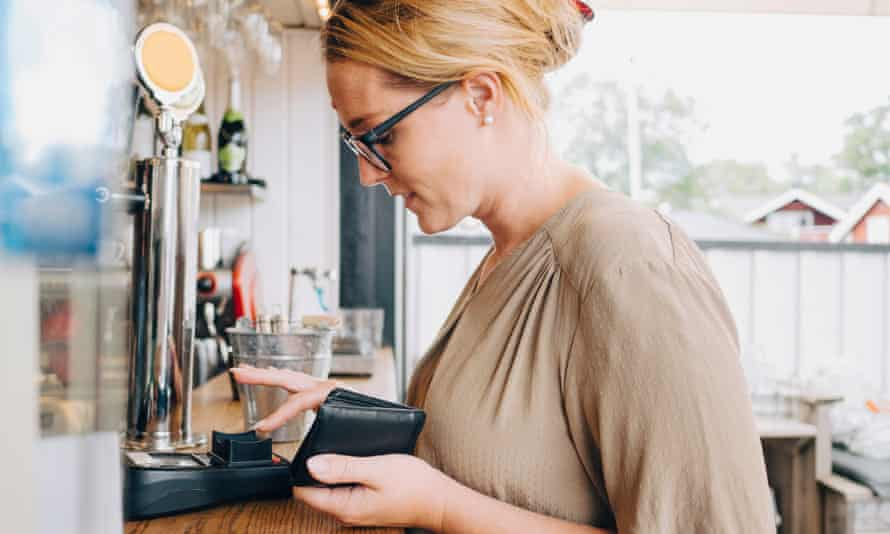 Female customer using credit card reader at checkout counter in restaurant