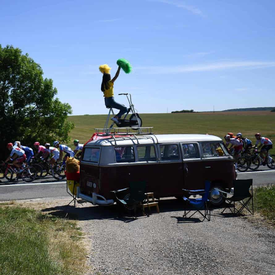 A woman cheers with pompoms from a car as the pack rides past on the fourth stage between Reims and Nancy.
