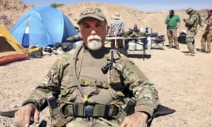Gerald (Jerry) DeLemus sits with a group of self-described militia members camping on Cliven Bundy''s ranch near Bunkerville.