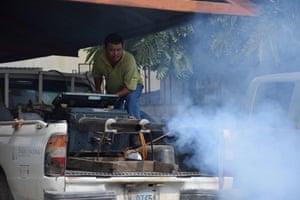 Marcio Mencia, an environmental health technician, operates a fumigation truck