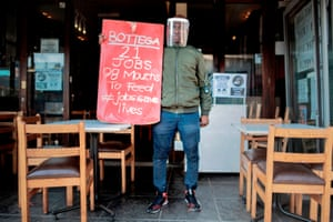 The manager of a restaurant in Parkhurst, Johannesburg, holds a banner during a national protest against the lockdown.