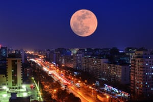 A Super Blood Moon rises over buildings in Beijing, China