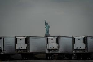 Statue of Liberty behind coronavirus temporary refrigerated morgue trailers.
