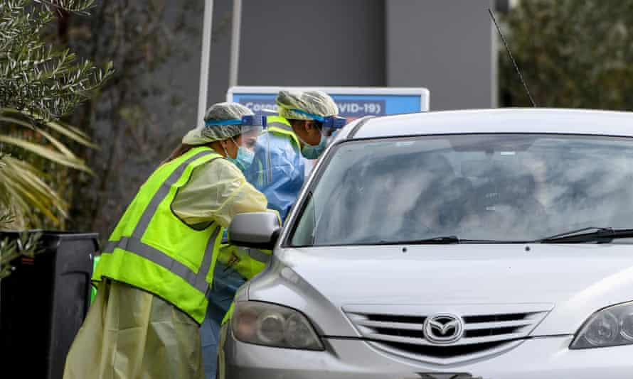 NSW Health workers administer coronavirus tests to people in their cars at the Crossroads Hotel in Casula, south-west Sydney.