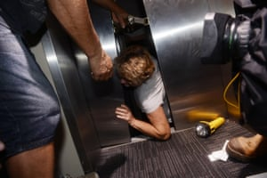 A woman scrambles out of a broken lift after Cyclone Marcia cut power to the Yeppoon hotel.