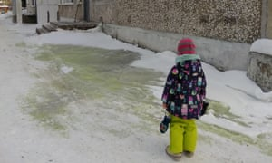 A girl stands near green snow in Pervouralsk, Russia.
