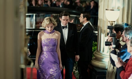 Emma Corrin as Diana and Josh O'Connor as Charles in character, walking through a grand doorway.