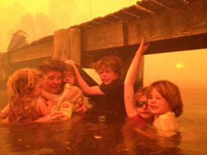 Tammy Holmes and her grandchildren Charlotte, Esther, Liam, Matilda and Caleb take refuge under a jetty as a wildfire rages nearby in the Tasmanian town of Dunalley, east of the state capital of Hobart, Australia. 4 January 2013.