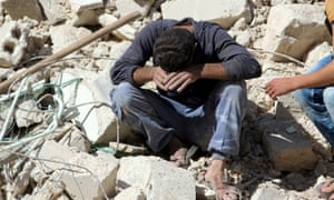 A man sits in the rubble of a damaged buildings after losing relatives in an airstrike, October 2016.