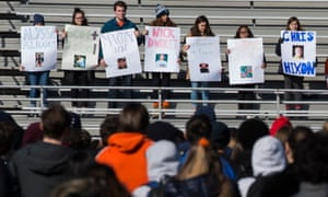 Students with pictures of those killed in the Parkland shooting during a school walk-out in Arlington, Virginia on March 14.