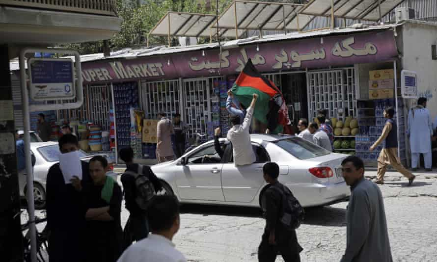 Afghans wave the national flag from a car in Kabul