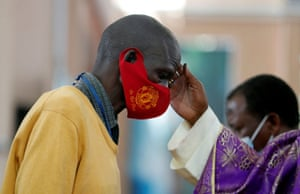 Cardinal John Njue marks a cross on the forehead of a man during mass at the Cathedral Basilica of the Holy Family in Nairobi, Kenya