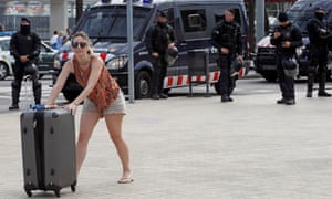 A tourist walks to Barcelona's cruise terminal as riot policemen keep watch after the protesters.