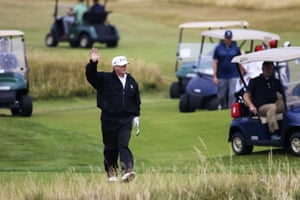 Trump waves to protesters while playing at Turnberry.